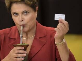 Brazil's President and Workers Party presidential candidate Dilma Rousseff, shows her electronic voting receipt that confirms she voted in the presidential runoff election as she drinks mate, an herbal tea, in Porto Alegre, Brazil, Sunday, Oct. 26, 2014. Rousseff is counting on Brazilians' gratefulness for a decade of progress to overcome concerns about a sluggish economy as the South American leader seeks re-election on Sunday after a bitter, unpredictable campaign. (AP Photo/Felipe Dana)