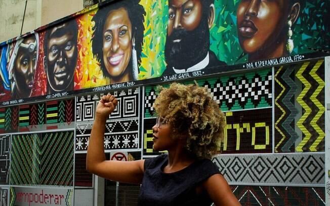 Letícia Gabriela em frente a fachada da Educafro com mural da Marielle
