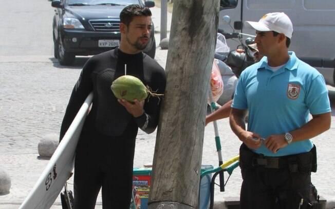 Cauã Reymond conversa com segurança enquanto se refresca com água de coco