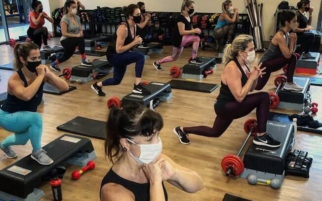 Alunos da academia BodyTech fazendo exercício com máscara