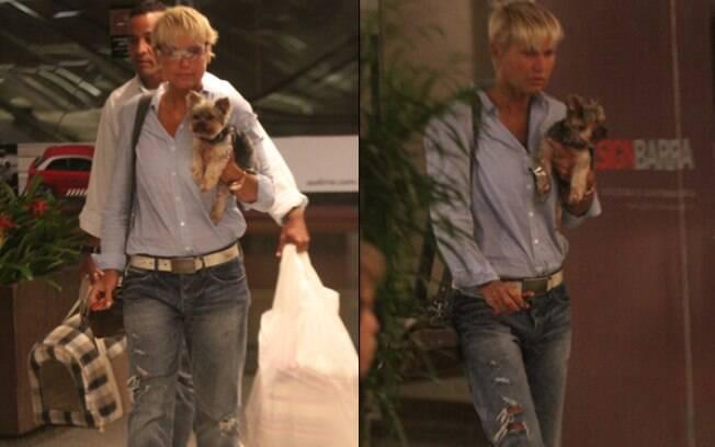 Xuxa recebe a ajuda de um segurança para carregar as sacolas