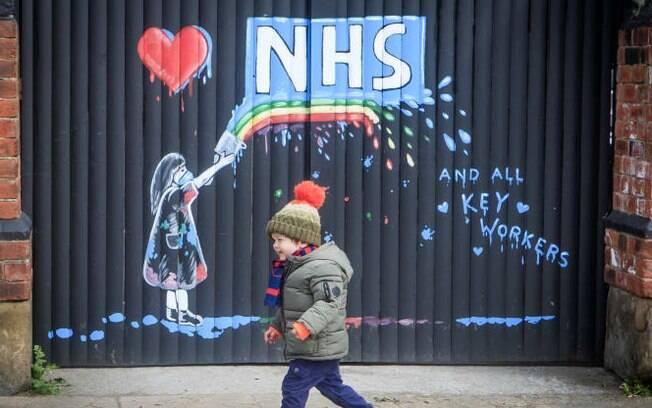 Um garoto passa por um mural apoiando o NHS, da artista Rachel List, nos portões do pub Hope & Anchor, em Pontefract, Yorkshire, enquanto o Reino Unido está confinada