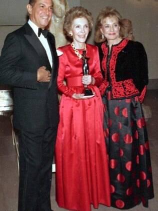 A primeira-dama Nancy Regan (de vermelho), em foto de 1989 com Oscar de la Renta, gostava de pegar roupas e joias emprestados