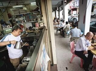 Tang Chew Fue, dono do Tong Ah Eating House, um kopitiam preparando um típico café da região