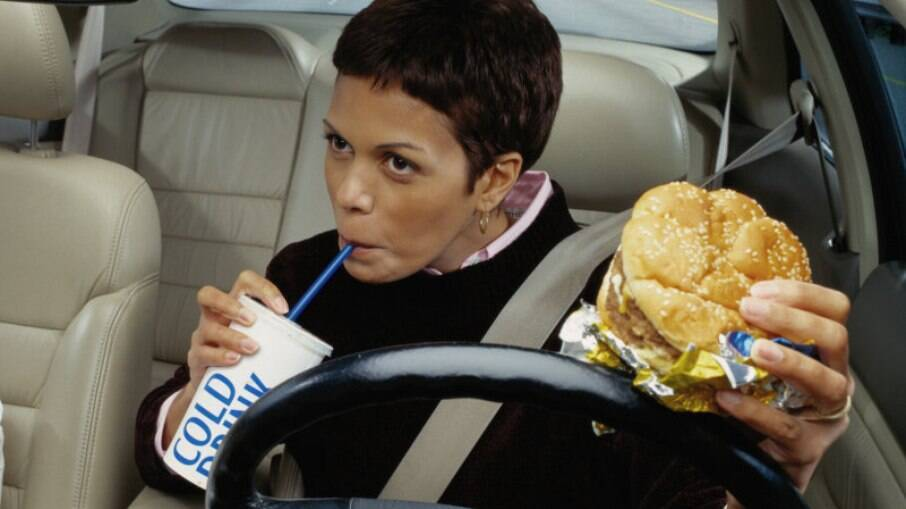 Comer ao volante se encaixa na mesma categoria de fumar, com 4 pontos na CNH e mais R$ 130,16
