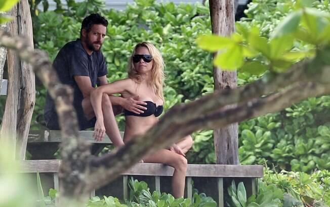Pamela Anderson com o namorado Jon Rose: mão boba