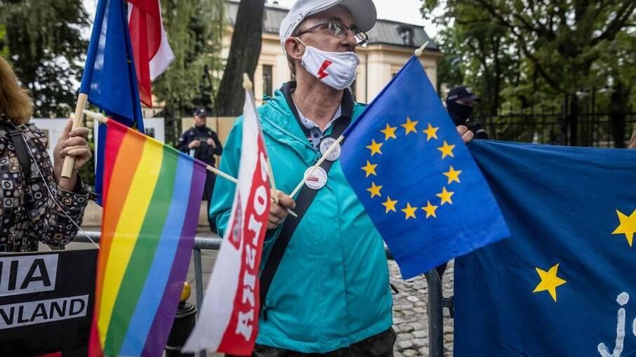 Um manifestante segura bandeiras LGBTQIAP+, da Polônia e da UE durante protesto em frente ao Tribunal Constitucional em Varsóvia