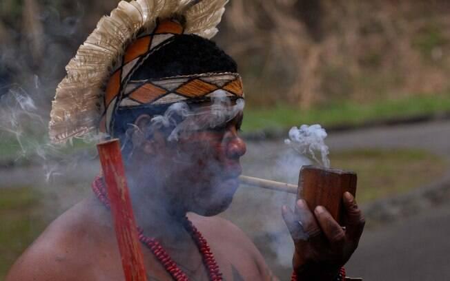 Indígena em ritual com uso de cachimbo
