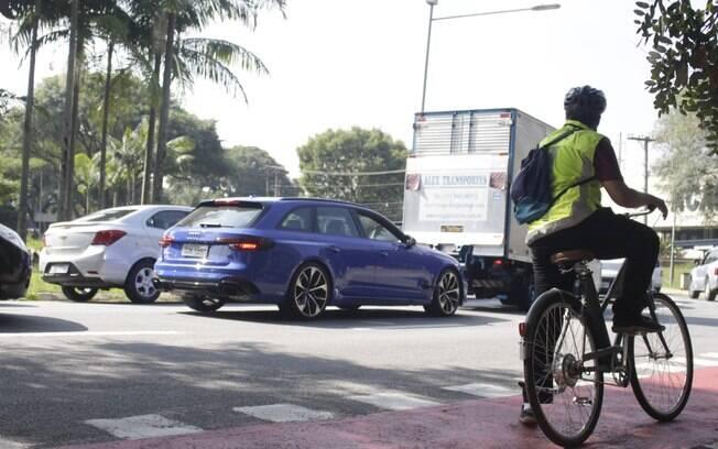 Audi RS4 Avant parada no congestionamento ao lado da bicicleta elétrica na ciclovia, com caminho livre pela frente