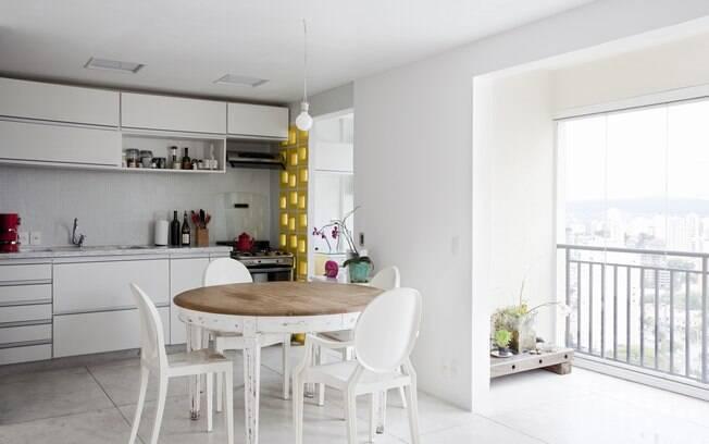 Parede amarela de elemento vazado faz a divisão entre cozinha e lavanderia neste apartamento projetado pelo Sub Estudio