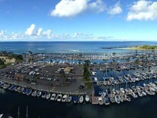 Cenário. Famosa e bela praia de Waikiki, em Honolulu, e os barcos na marina em Ala Wai