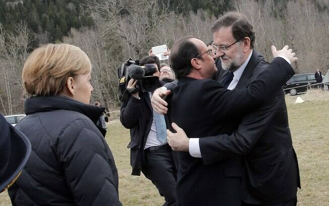 Mariano Rajoy (à direita) é observado por Merkel enquanto cumprimenta François Hollande