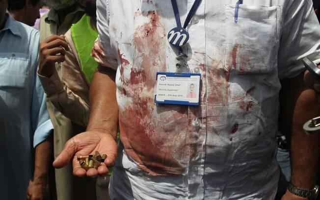 Oficial paquistanês mostra cartuchos recolhidos na cena do ataque ao ônibus, em Karachi