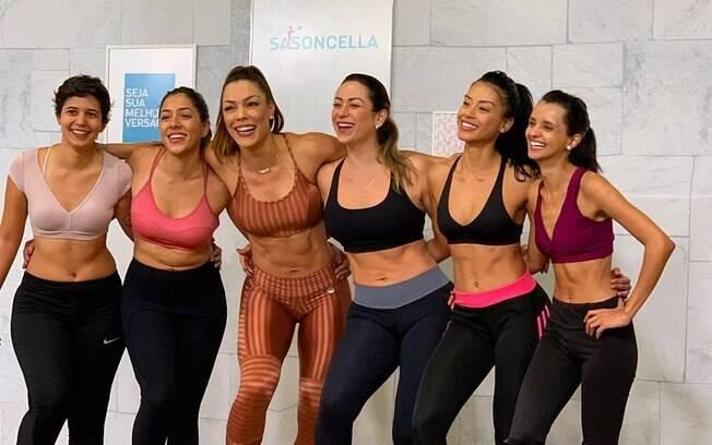 seis mulheres com roupa de ginástica se abraçam