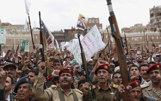 Rebeldes xiitas conhecidos como houthis levantam suas armas para protestar contra os ataques aéreos sauditas em Saana, Iêmen (26/03)
