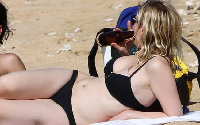Kirsten Dunst bebe cerveja em praia no Havaí