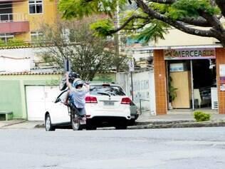 Rapaz empina a moto pela rua quando vê que está sendo fotografado