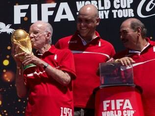 Brazil's former World Cup champion Zagallo, left, kisses the the FIFA World Cup trophy as his fellow World Cup champion winners Marcos, center, and Rivellino stand with him at the opening ceremony of the FIFA WCUP Trophy Tour in Rio de Janeiro, Brazil, Thursday, Sept. 12, 2013. The trophy is set to embark on an extensive journey, covering more than 80 countries, giving the opportunity to millions of fans to enjoy the authentic solid-gold trophy. (AP Photo/Silvia Izquierdo)