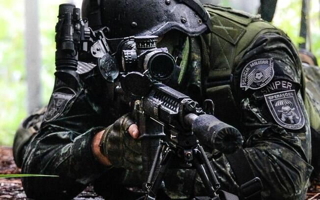 Atirador de Precisão (Sniper) posicionado e observando seu alvo. O dedo indicador direito está esticado, o Atirador irá colocar o dedo no gatilho apenas no momento do disparo. O braço esquerdo não toca no rifle para não transmitir nenhuma vibração que possa interferir no momento do tiro. Note o emblema