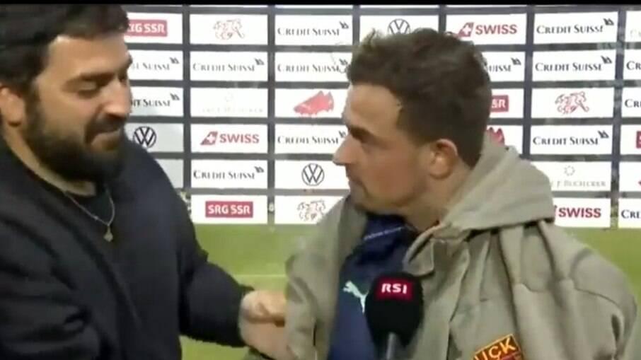 Homem invade entrevista e veste Shaqiri com casaco de organização militar