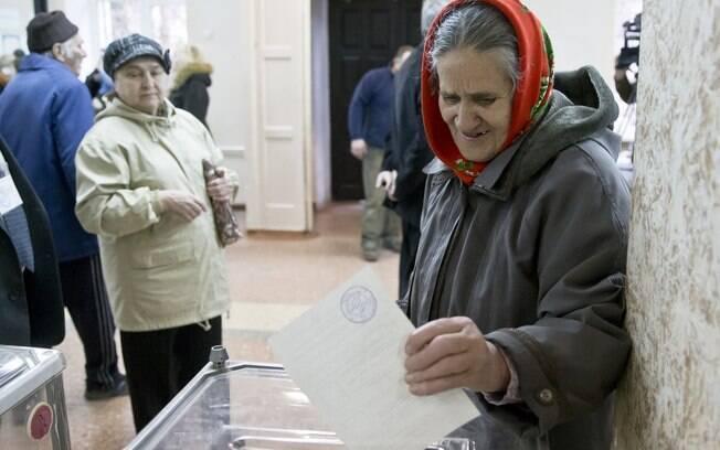 Mulher coloca cédula do referendo em urna eleitoral, durante votação em Simferopol, Ucrânia