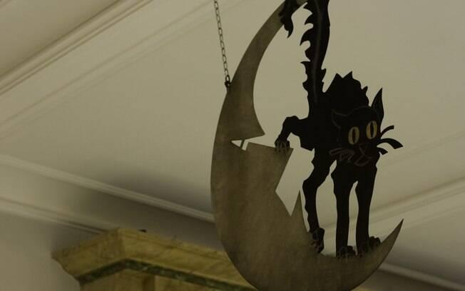 Gato preto assustado em uma lua crescente do famoso Chat Noir, cabaré de do século 19, no Musee Carnavalet