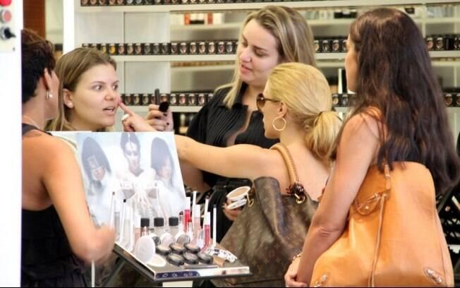 Carolina Dieckmann testa maquiagem em atendente de loja de beleza em shopping do Rio de Janeiro