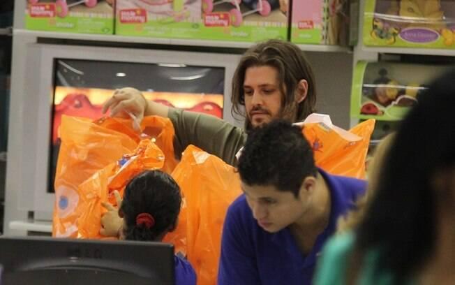 Dado Dolabella: carregado de sacolas a caminho do aniversário dos filhos