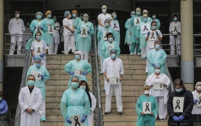 Profissionais usam máscaras protetoras enquanto observam um minuto de silêncio na entrada de um hospital em lembrança da equipe de enfermagem que morreu da Covid-19