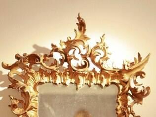 Espelho com moldura talhada e em tom dourado tem presença marcante