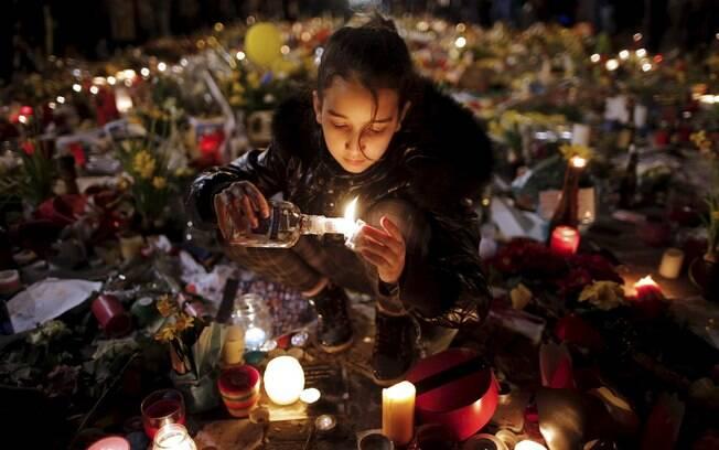 Criança homenageia vítimas dos atentados de Bruxelas, neste sábado, na Place de la Bourse