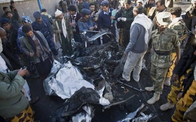 Investigadores de polícia do Iêmen perto dos destroços no local onde um carro bomba foi detonado perto de delegacia em Sanaa