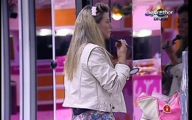 Fabiana se maquia com o auxílio do espelho