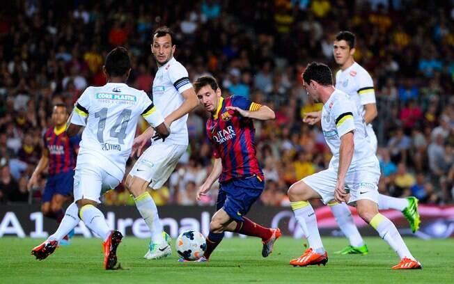 Quatro jogadores do Santos cercam Lionel  Messi no Camp Nou