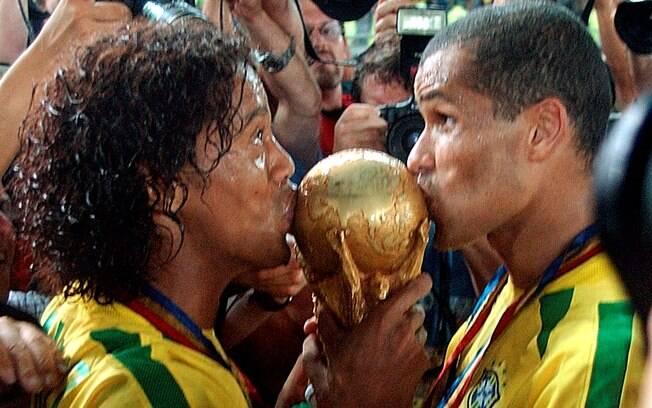 Ronaldinho beija a taça da Copa do Mundo de  2002, ao lado de Rivaldo