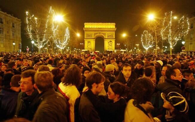 Foliões se reúnem na avenida Champs Elysées para comemorar a virada, mesmo sem música e fogos de artifício