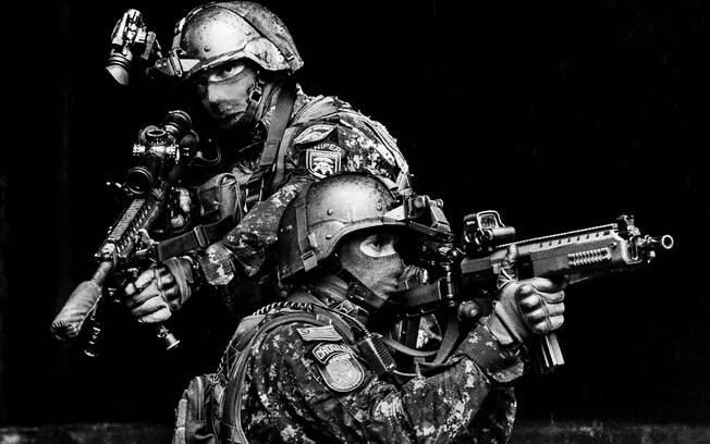 O Policial COE da frente segura um rifle de assalto, dando cobertura para o Atirador de Precisão (Sniper), logo atrás. Note a diferença do comprimento do cano e tamanho das miras telescópicas das duas armas. O Atirador possui o emblema