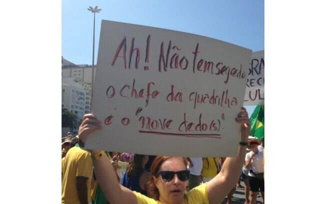 Mulher exibe cartaz durantes as manifestações de 12 de abril
