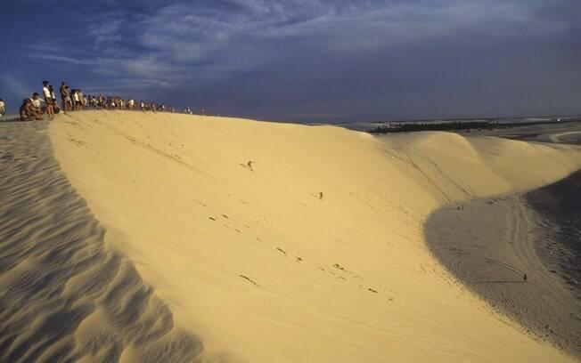 Turistas assistem pôr-do-sol do alto da duna