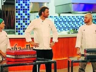 O apresentador Carlos Bertolazzi entre os dois chefs finalistas