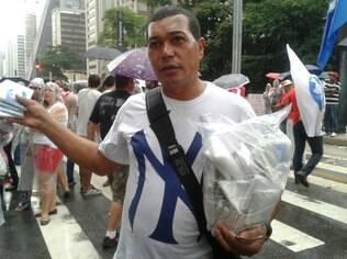 Manuel Marcos, de 50 anos, vende capas de chuva durante manifestação