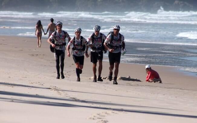 Equipe Segate, vice-campeã corre na areia ao  lado de turistas em Itacaré. Foram mais de 117 km  de trekking