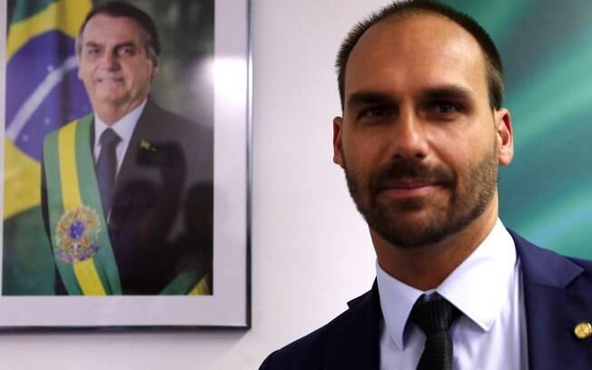 Eduardo Bolsonaro com quadro de seu pai, Jair Bolsonaro, ao fundo
