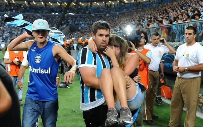 Torcedora é carregada após queda de grade na  comemoração do gol do Grêmio