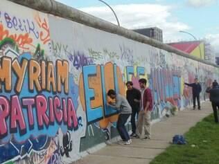 Jovens turistas deixam sua marca pelo Muro de Berlim
