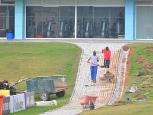 Funcionários trabalham na colocação de uma canaleta na rampa de acesso aos campos