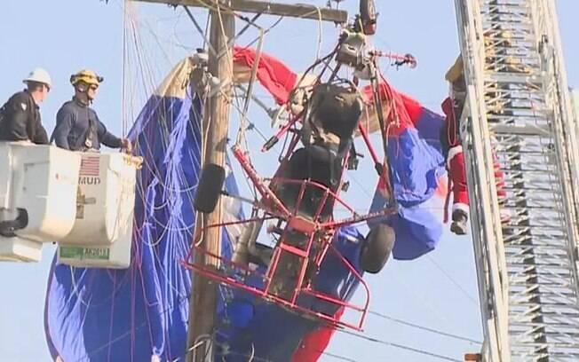 Vestido de papai noel, homem sofre acidente de paraglider e fica preso entre fios
