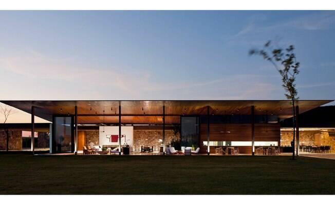 A casa BV de 1.880,50 m², em Porto Feliz, se destaca pelas grandes aberturas na arquitetura e pelo paredão de pedra (ao fundo). Destaque ainda para o telhado de madeira