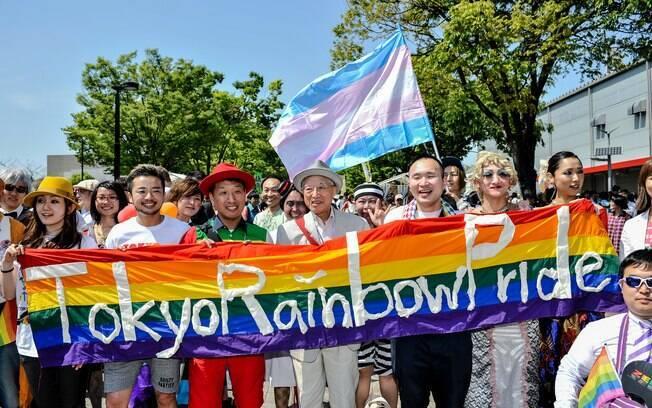 Participantes erguem bandeira durante a Parada Gay de Tóquio