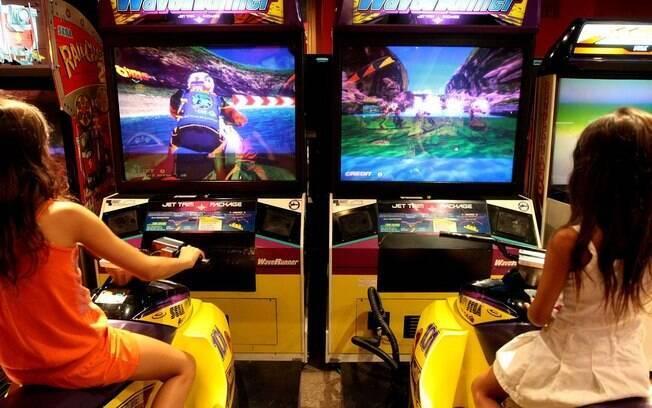 Crianças e adultos se divertem em brinquedos e jogos eletrônicos